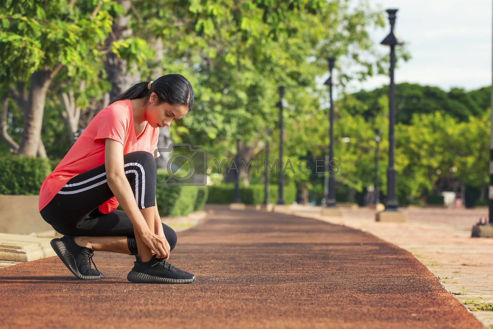 Beautiful woman is lacing a running shoe on the runway in the park before exercising for health care. Healthy concept