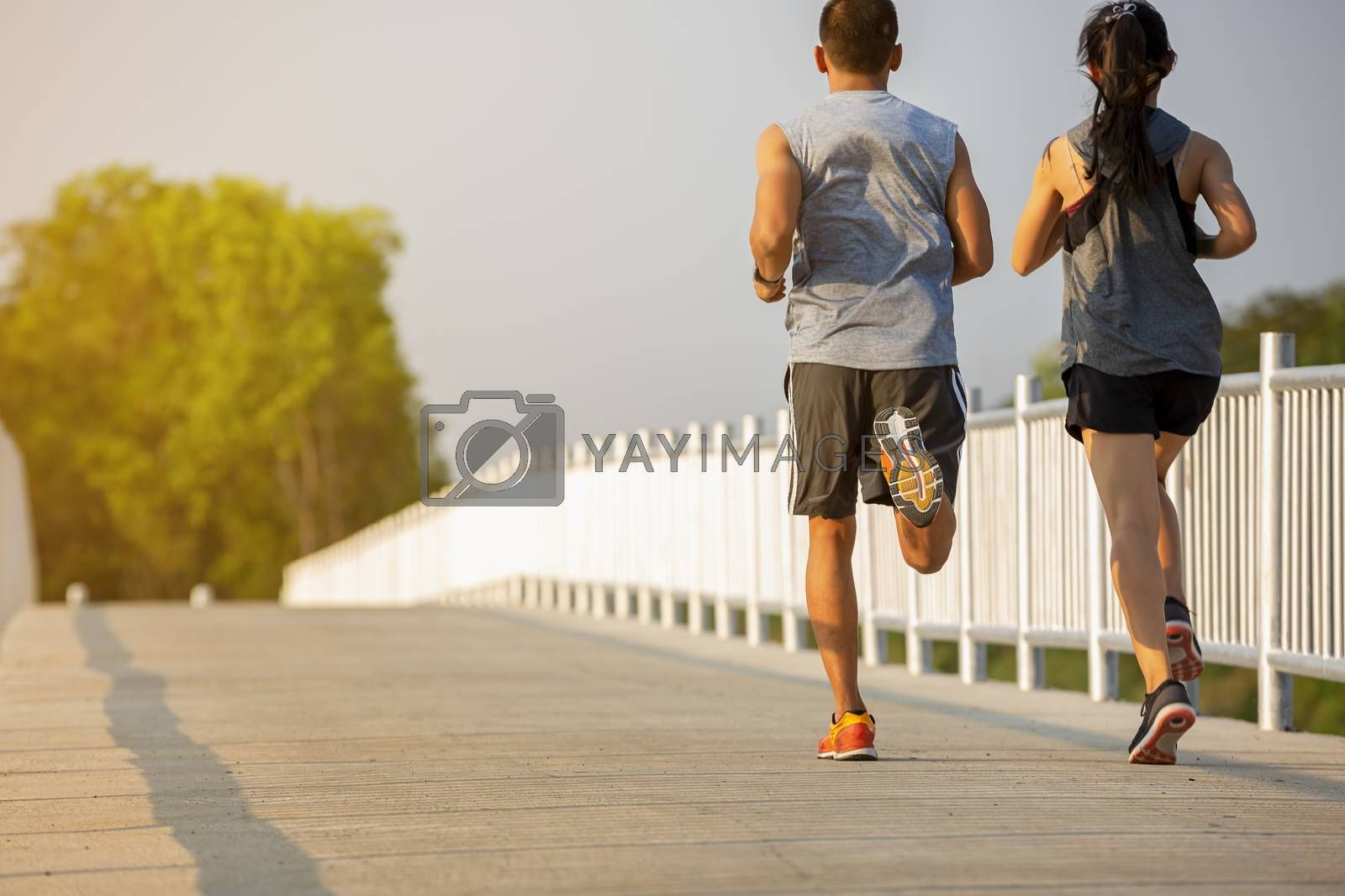Silhouette of a couple running and exercising at sunset with the sun in the background, colorful sunset sky
