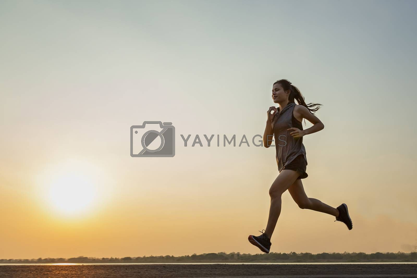 The silhouette of young women running and exercising at sunset w by numberone9018