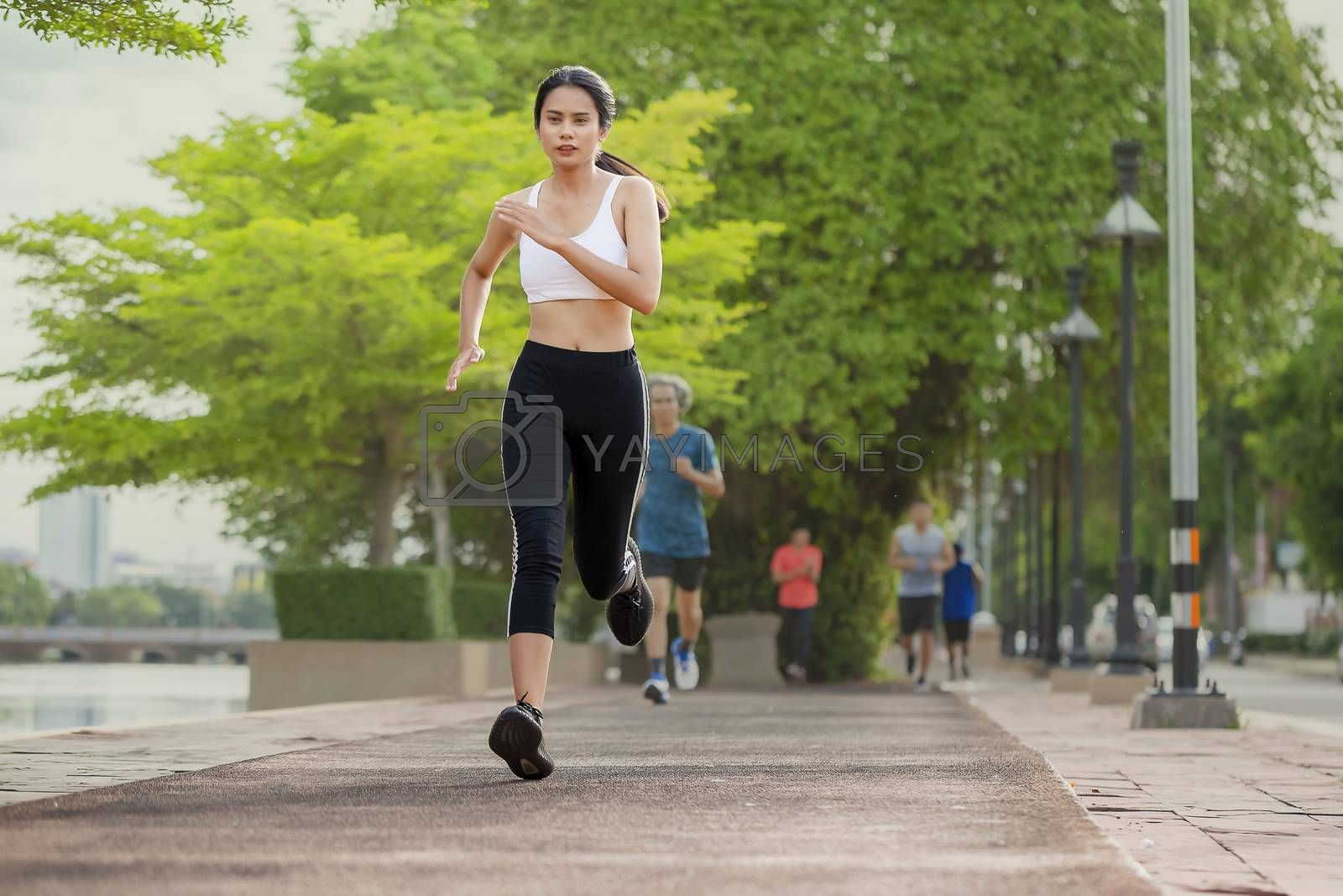 Portrait of beautiful woman running in the park in early morning. Healthy concept