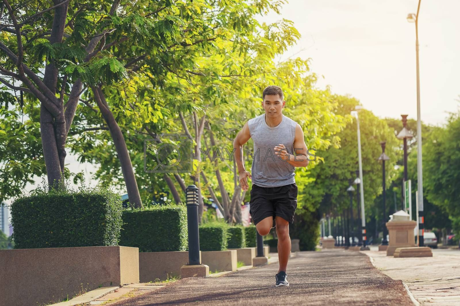Portrait of handsome man running in the park in early morning. Healthy concept