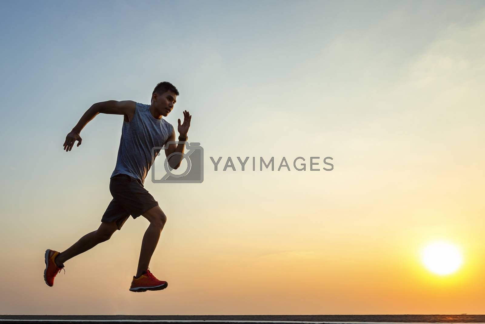 The silhouette of young men running and exercising at sunset with the sun in the background, colorful sunset sky