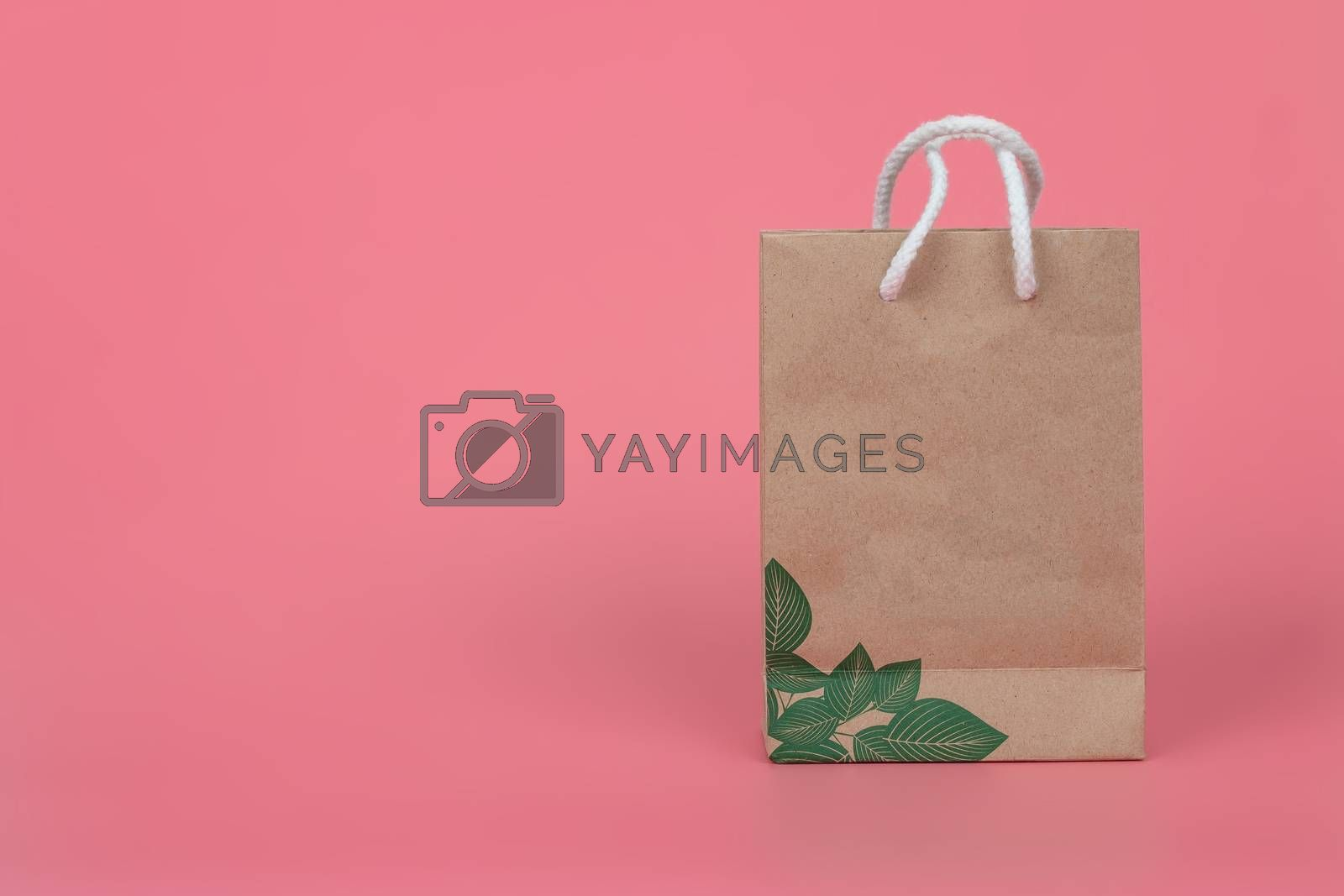 Paper bags on pastel pink backgrounds, environmental conservation concept