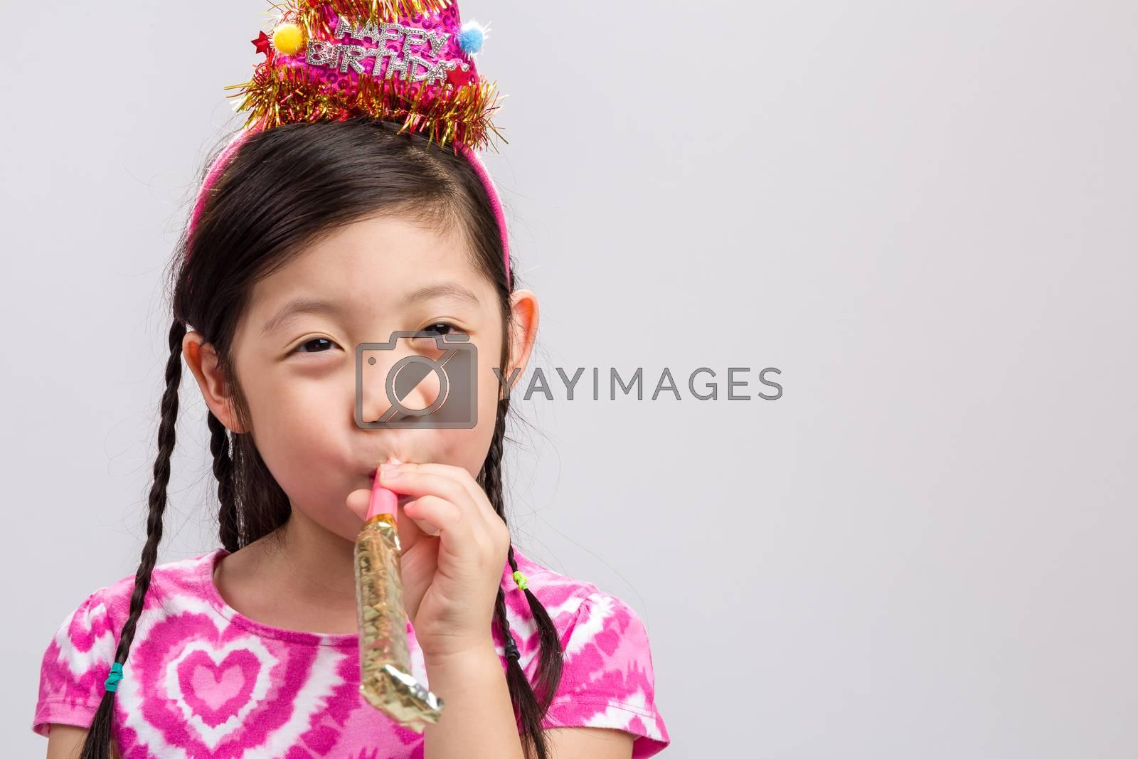 Little girl celebrates her birthday on isolated white background.