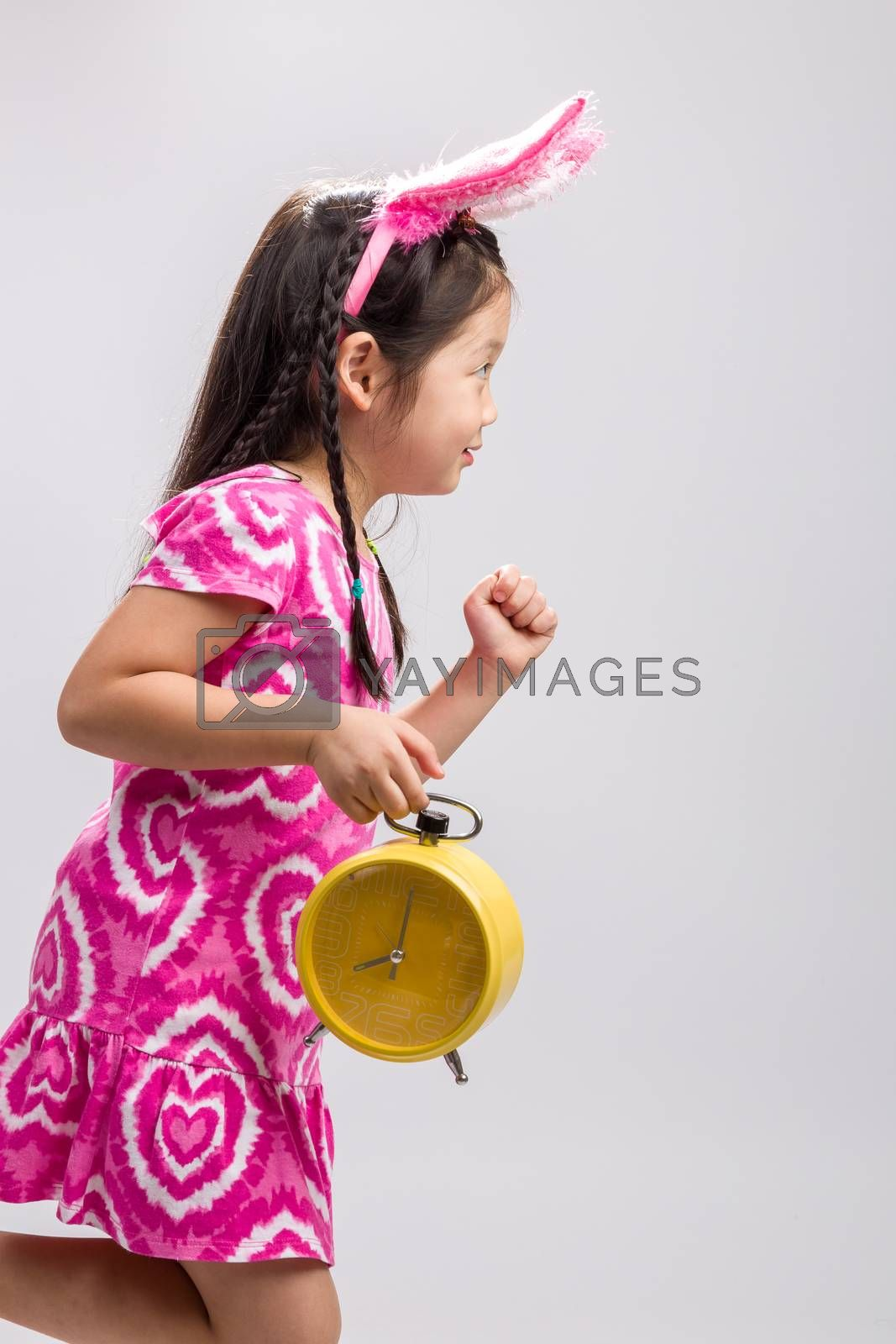 Child holding clock illustrating time concept on white background.