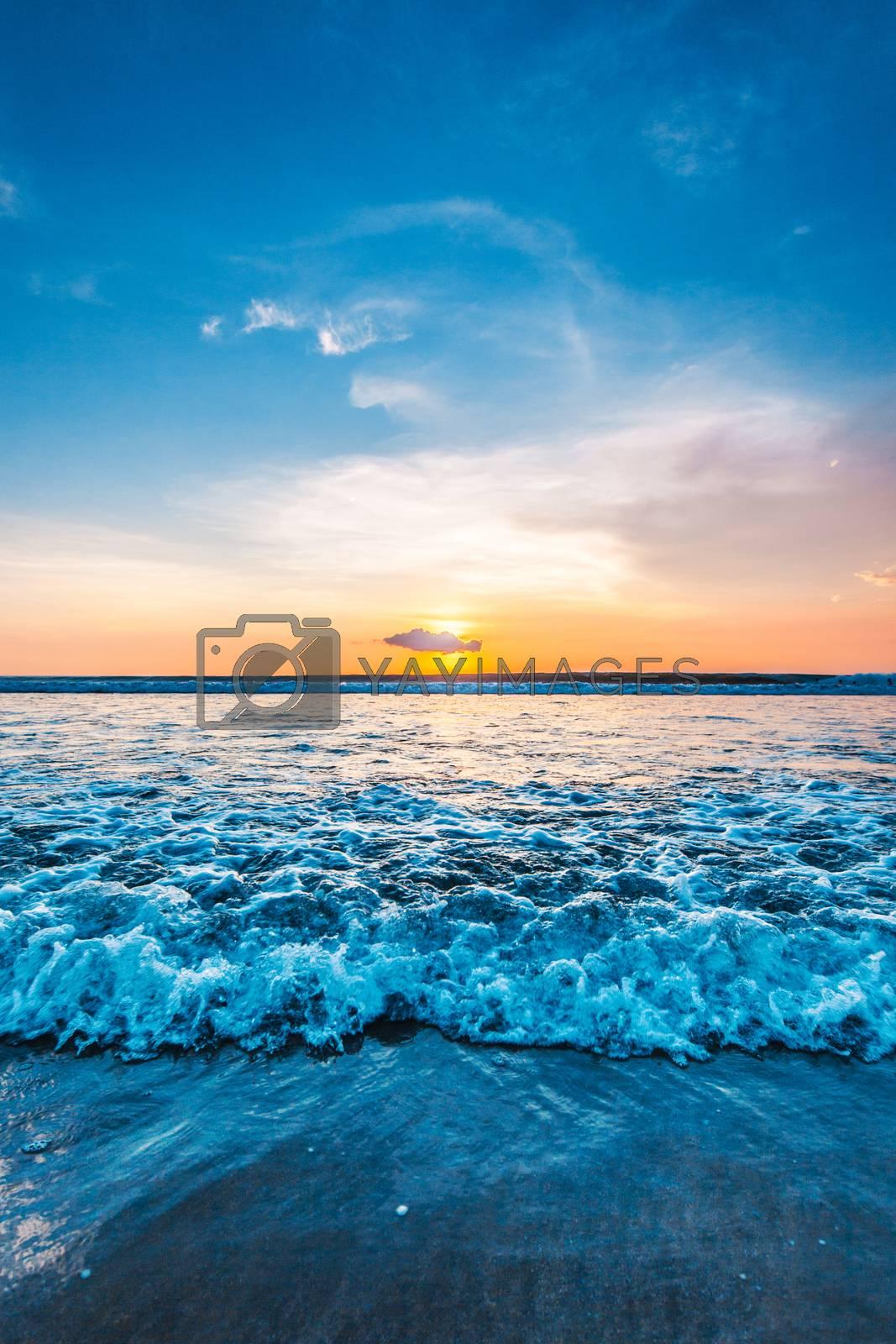 Sea waves at sandy beach at sunset, sun hiding behind a cloud