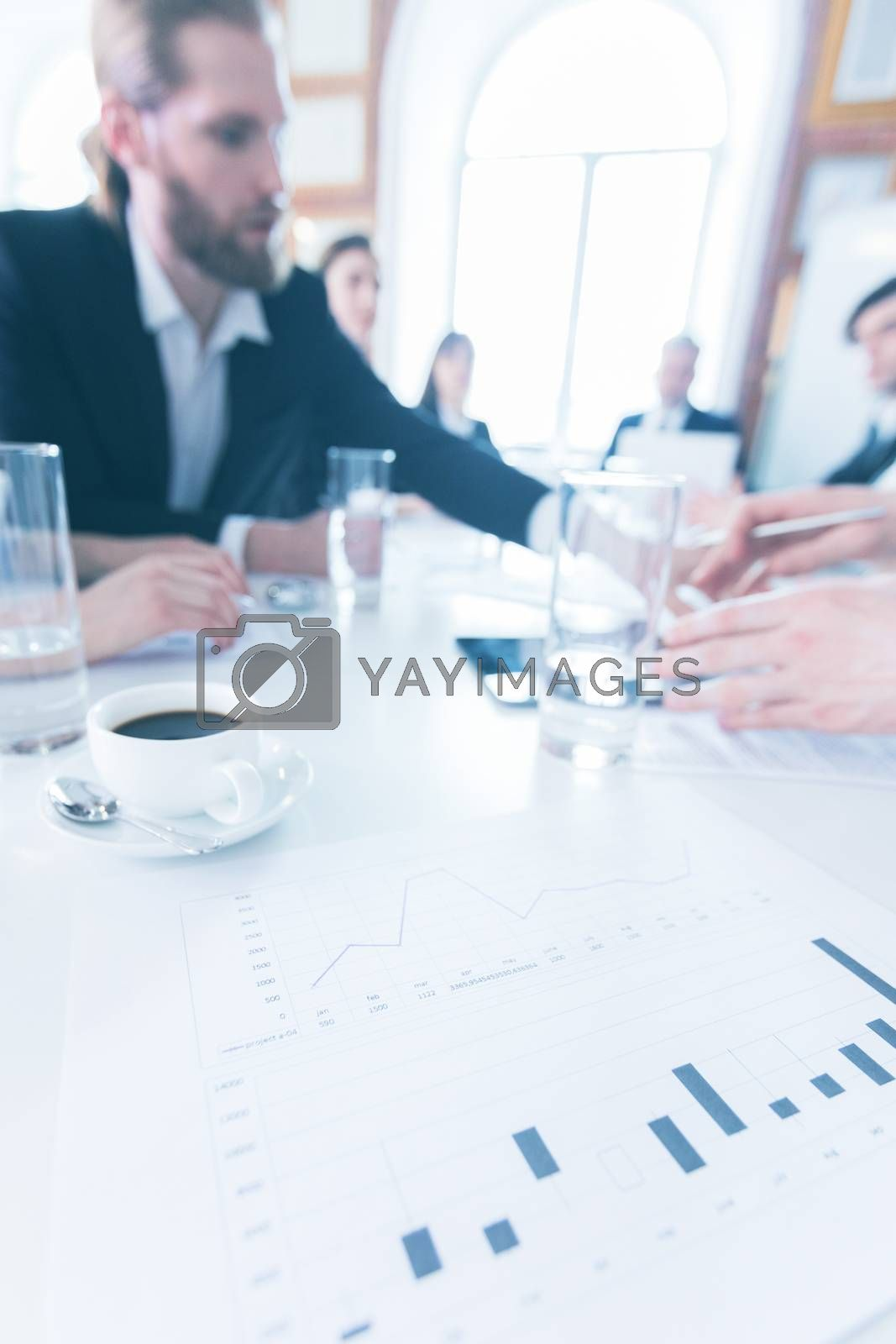 Business documents statistics data on office table and team of business people on background