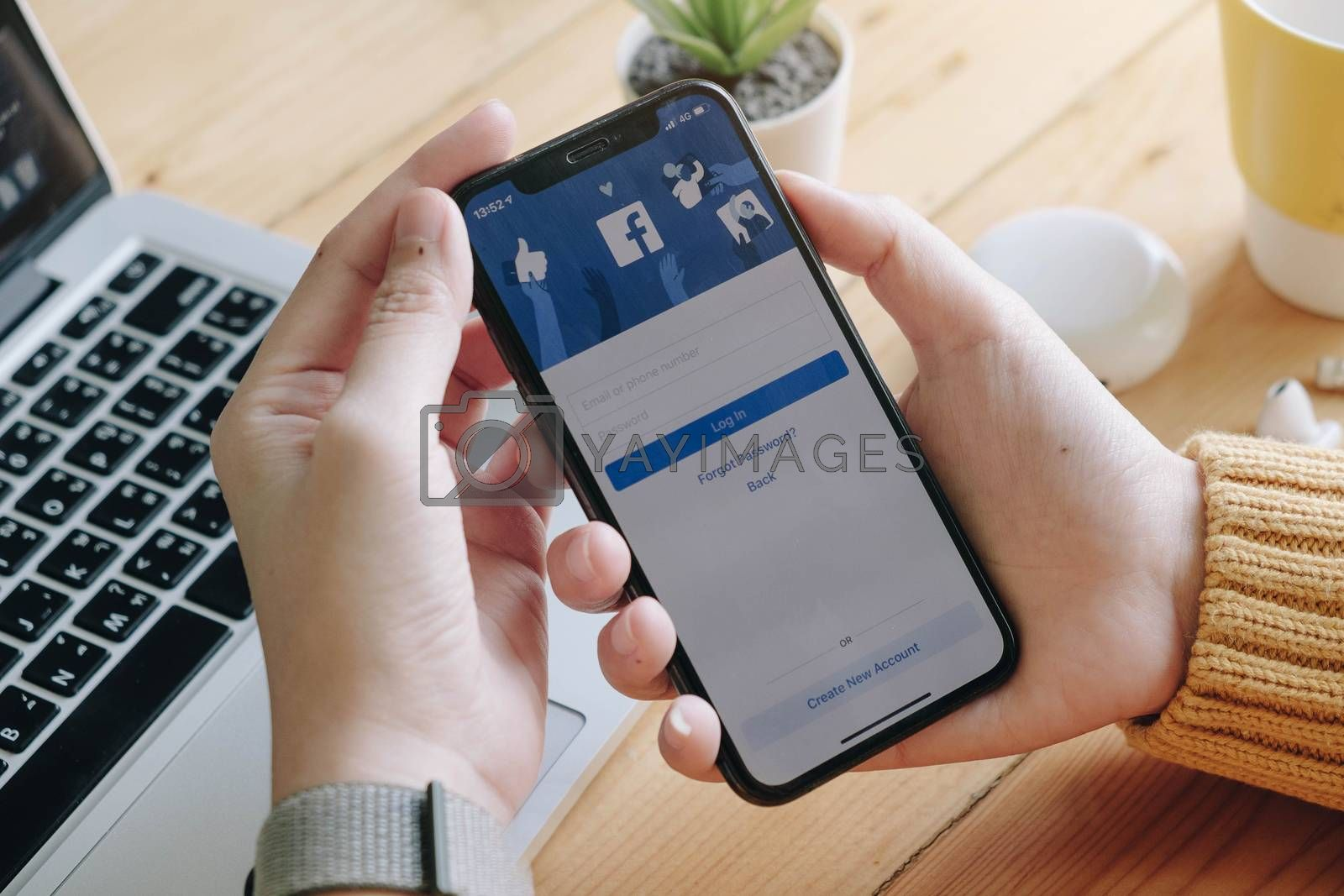 CHIANG MAI, THAILAND - JUN 7, 2020: Facebook social media app logo on log-in, sign-up registration page on mobile app screen on iPhone X (10) in person's hand working on e-commerce shopping business