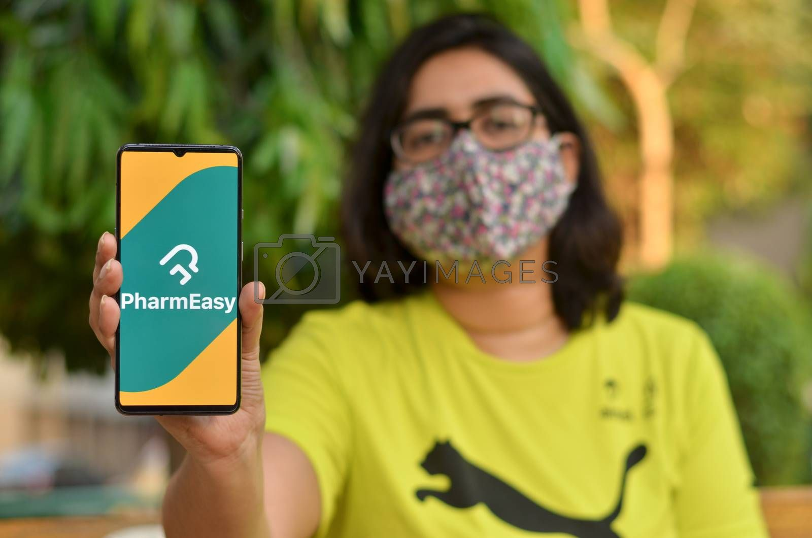 New Delhi, India, 2020. Girl wearing mask with Pharmeasy app on the mobile phone. Only essential services / products are allowed to be delivered during Corona Virus (Covid-19) lockdown by jayantbahel