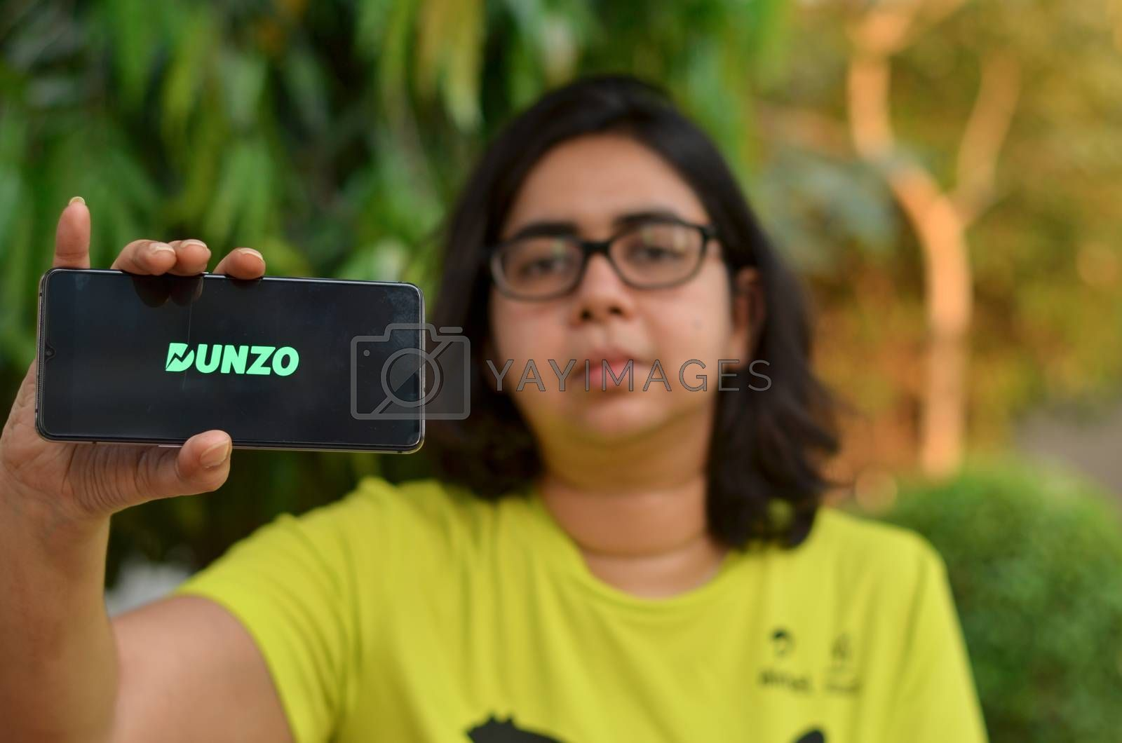 Mumbai, India, 2020. Young Girl with Dunzo Delivery app logo glowing on the mobile phone screen in her hands. Selective focus and shallow depth of field. The main focus is on the logo.