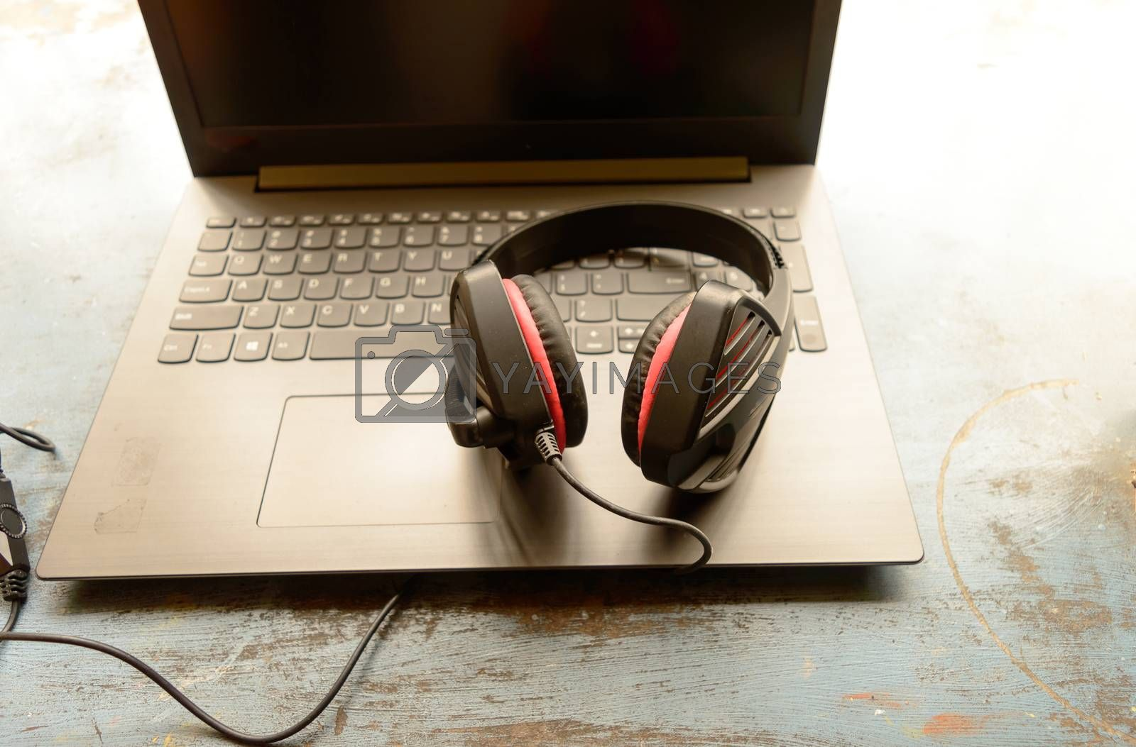 Portable over-ear Binaural Sound USB Headset with Microphone Noise Cancelling and Ultrasonic Volume Adjuster Headphone for Computer, Skype placed on laptop on morning sunlight. Music Background.