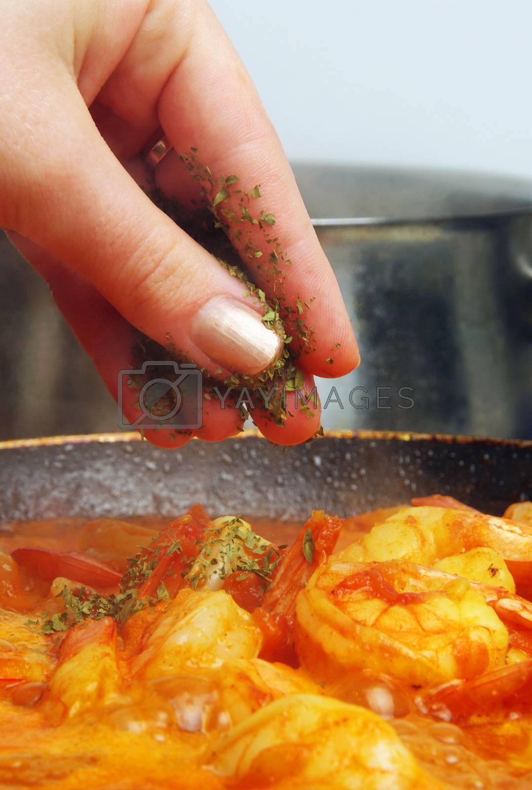 adding herbs to delicious prawns