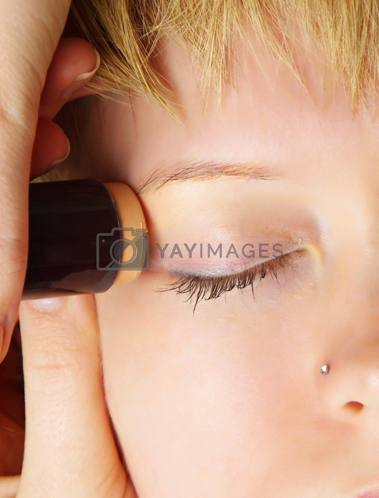 closeup of woman doing eyes treatments