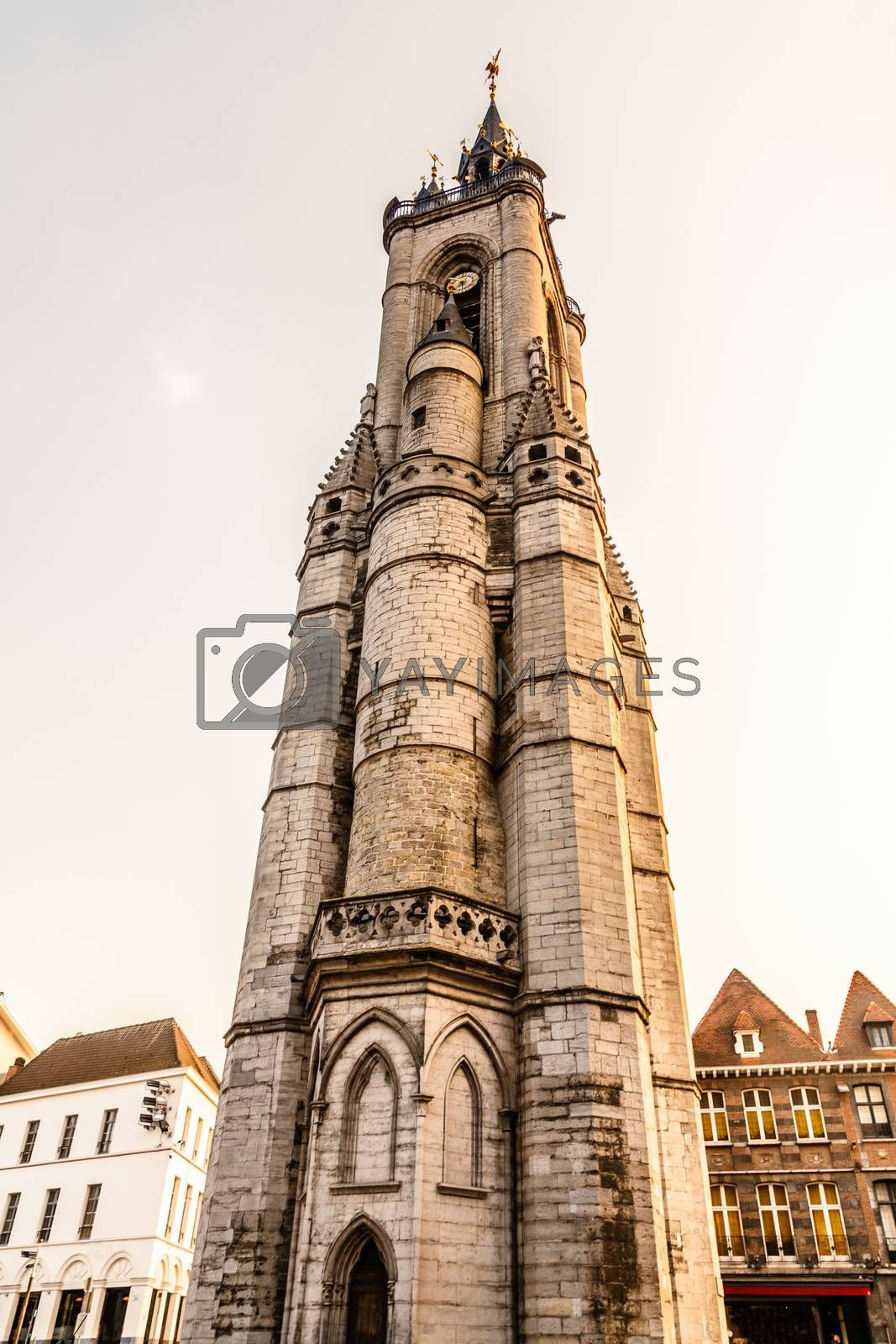 Tall medieval bell tower rising over the street with old european houses, Tournai, Walloon municipality, Belgium