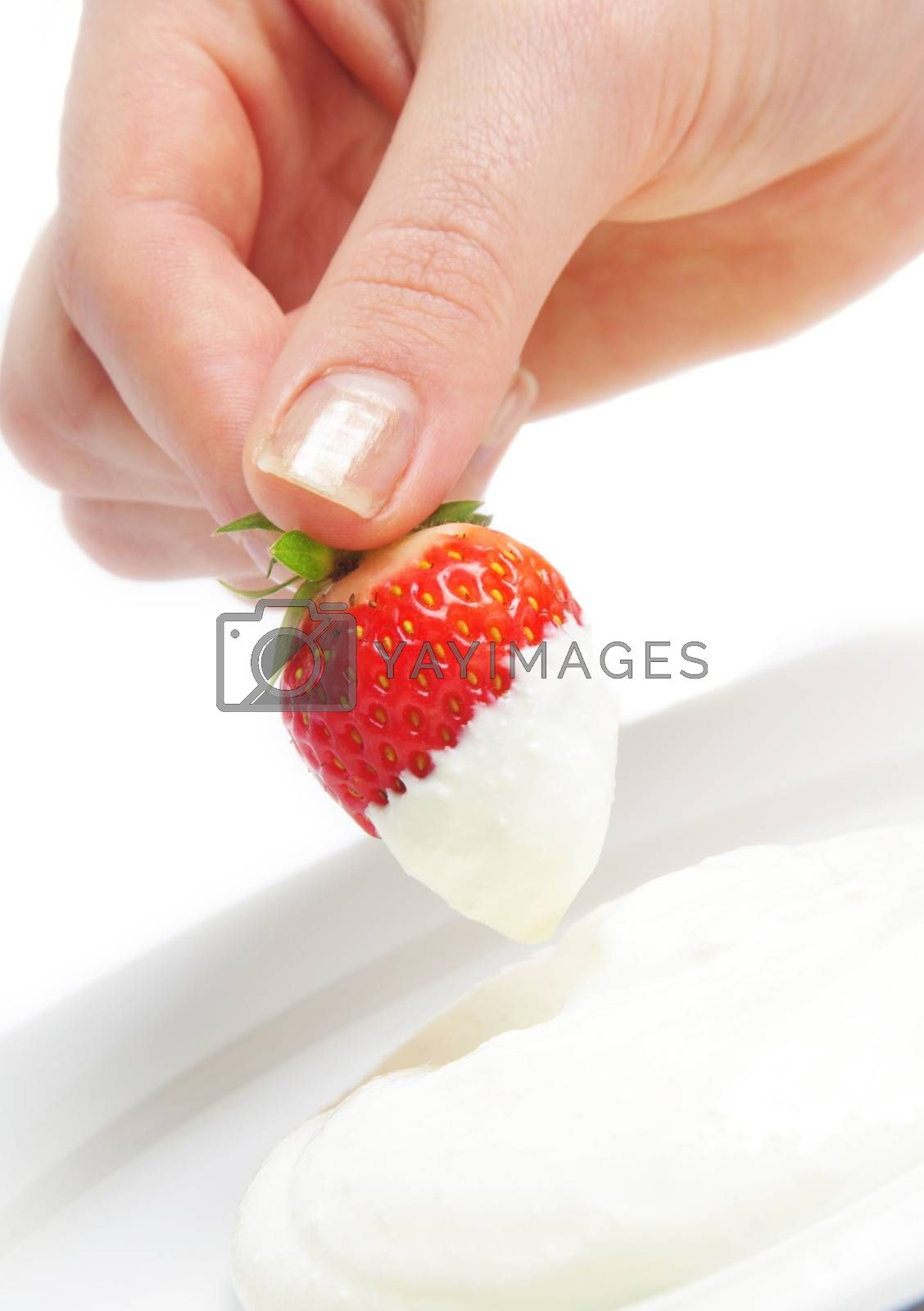 strawberry in hand with cream over white