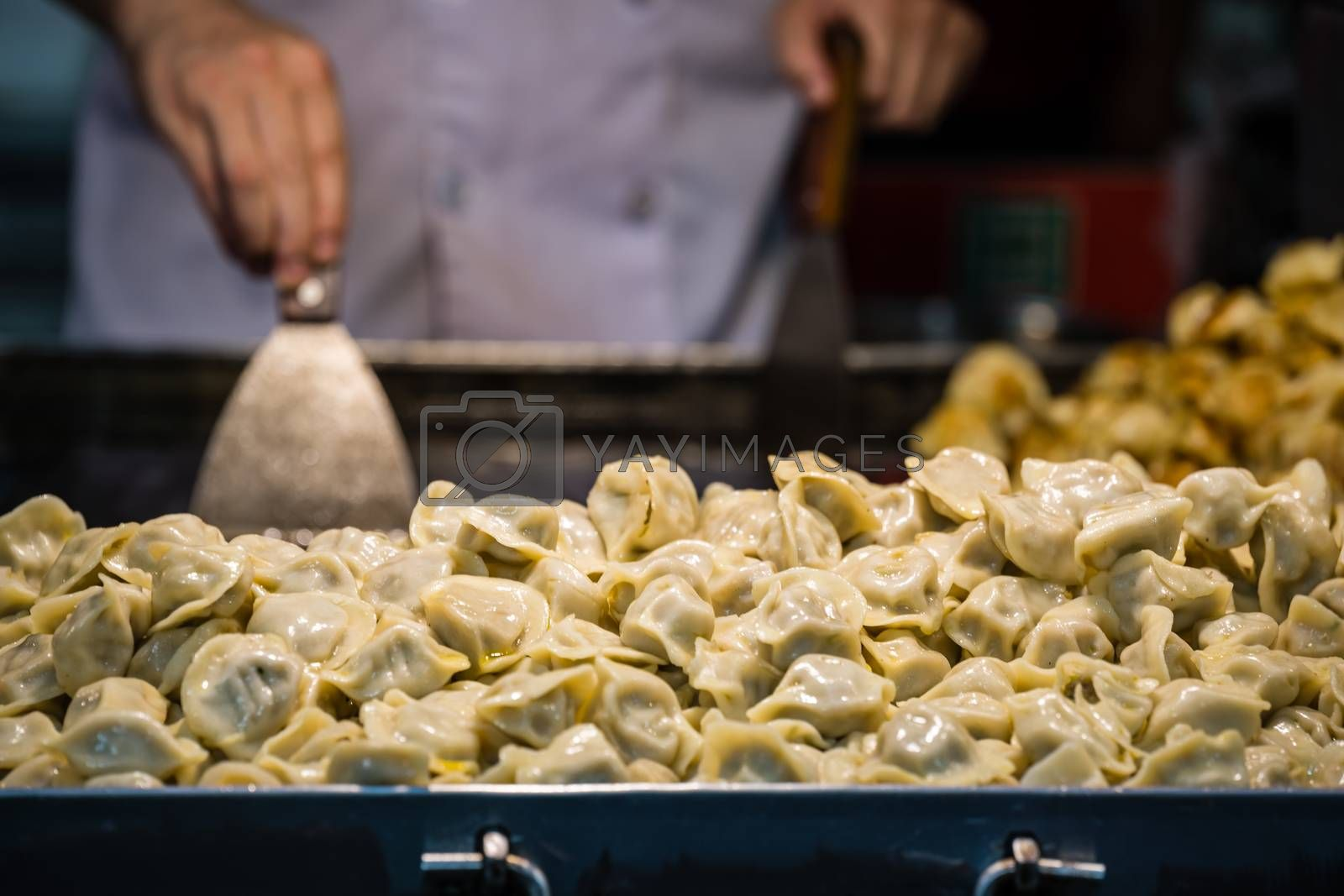 Delicious traditional chinese dumplings filled with pork meat, prepared on hot plate on a street stand, China