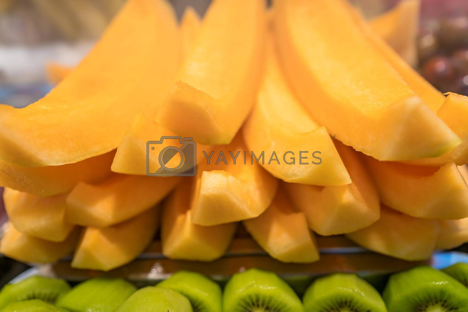 Pile of freshly cut delicious juicy kiwis and melons for sale on market in China