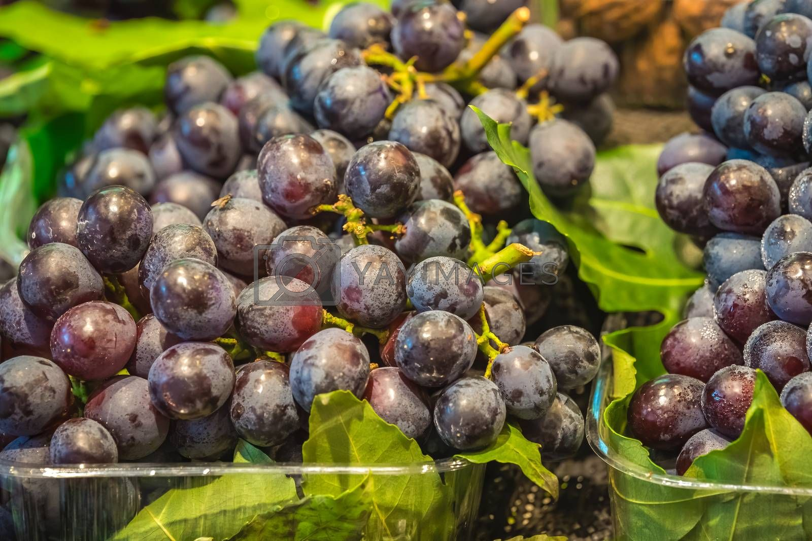 Pile of fresh and delicious dark red grapes for sale on market in China