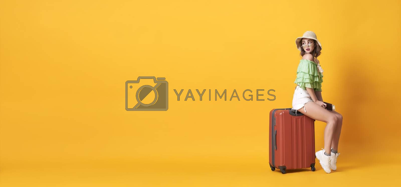 Cheerful young woman dressed in summer clothes holding passport with suitcase over yellow banner background with copy space.