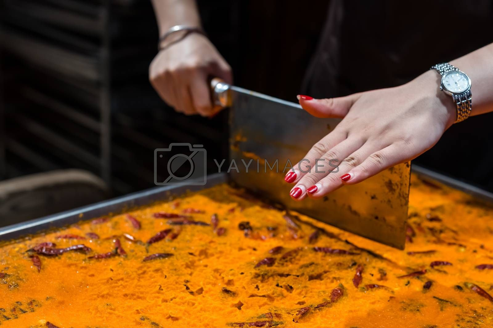 Royalty free image of A female cutting a strange oriental dessert into slices by pawopa3336