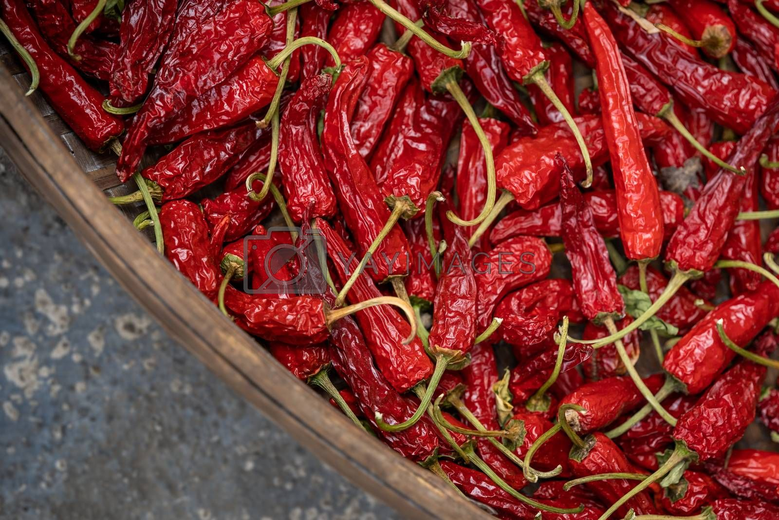 Chillies drying in a large round wicker bowl in a cellar basement of an old house in a small mountain village in China