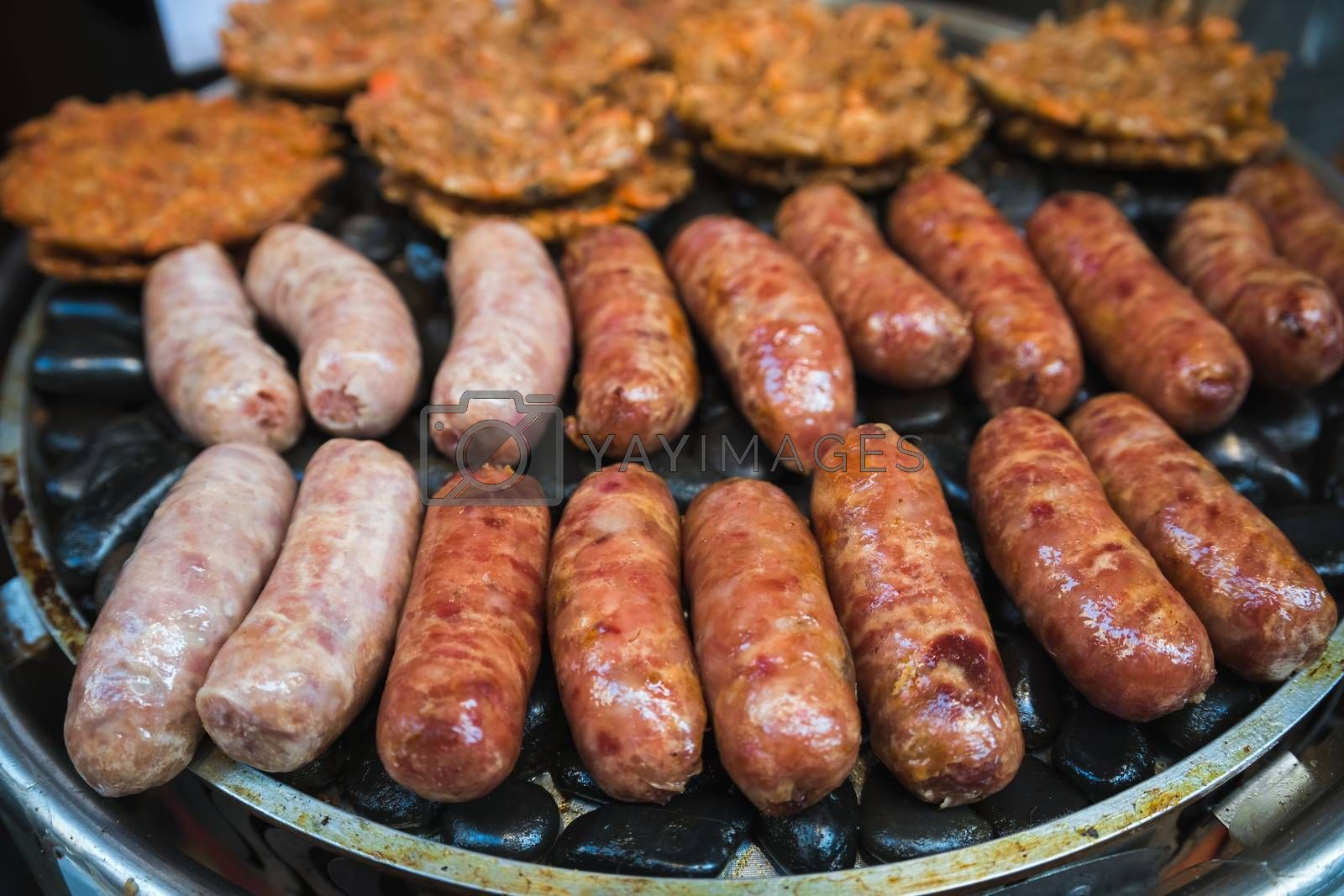 Royalty free image of Frying sausages on a grill on a chinese market stall by pawopa3336