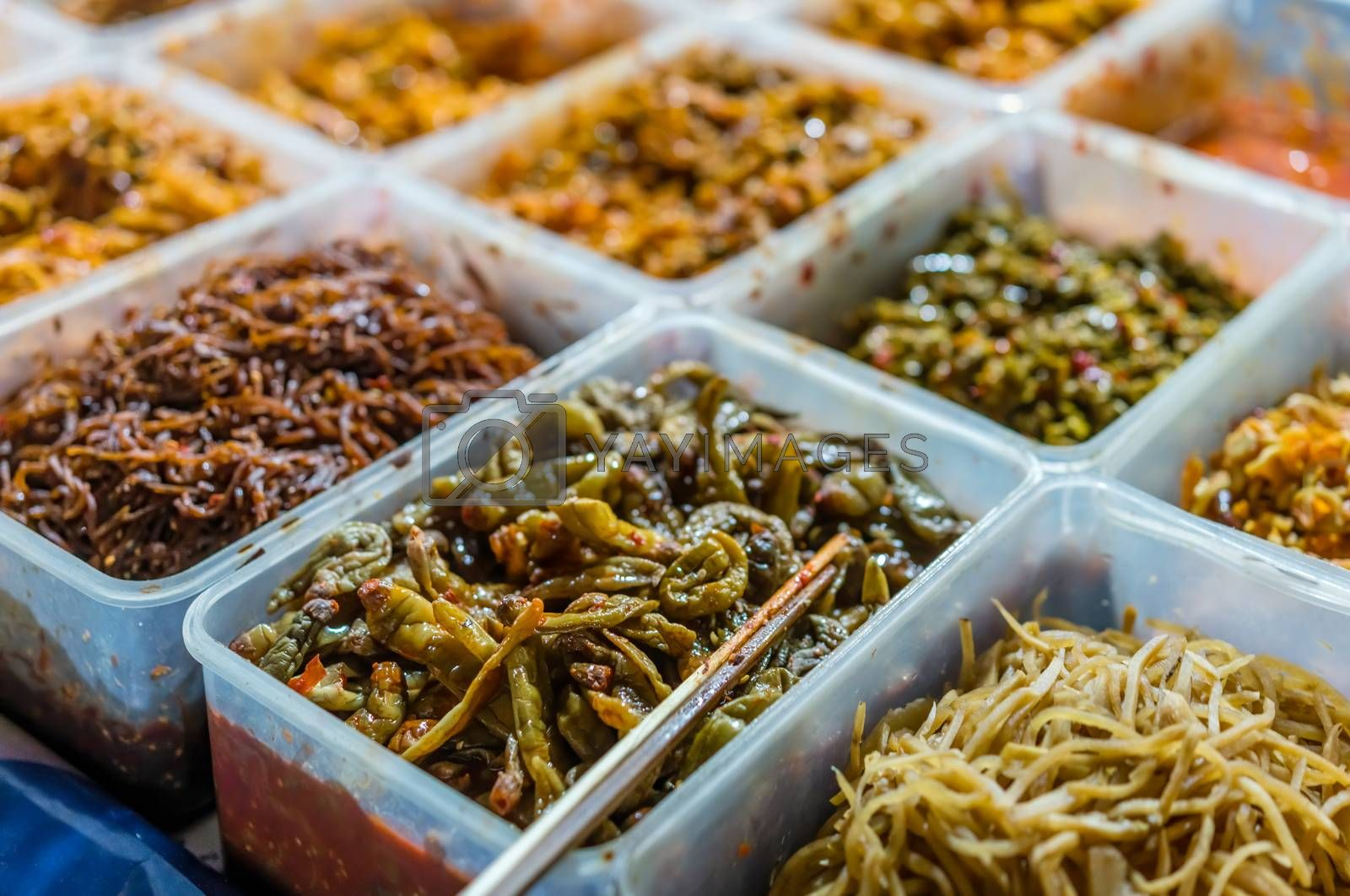 Buffet of plastic boxes with spicy additions to food ordered from an outdoor street food stall, China