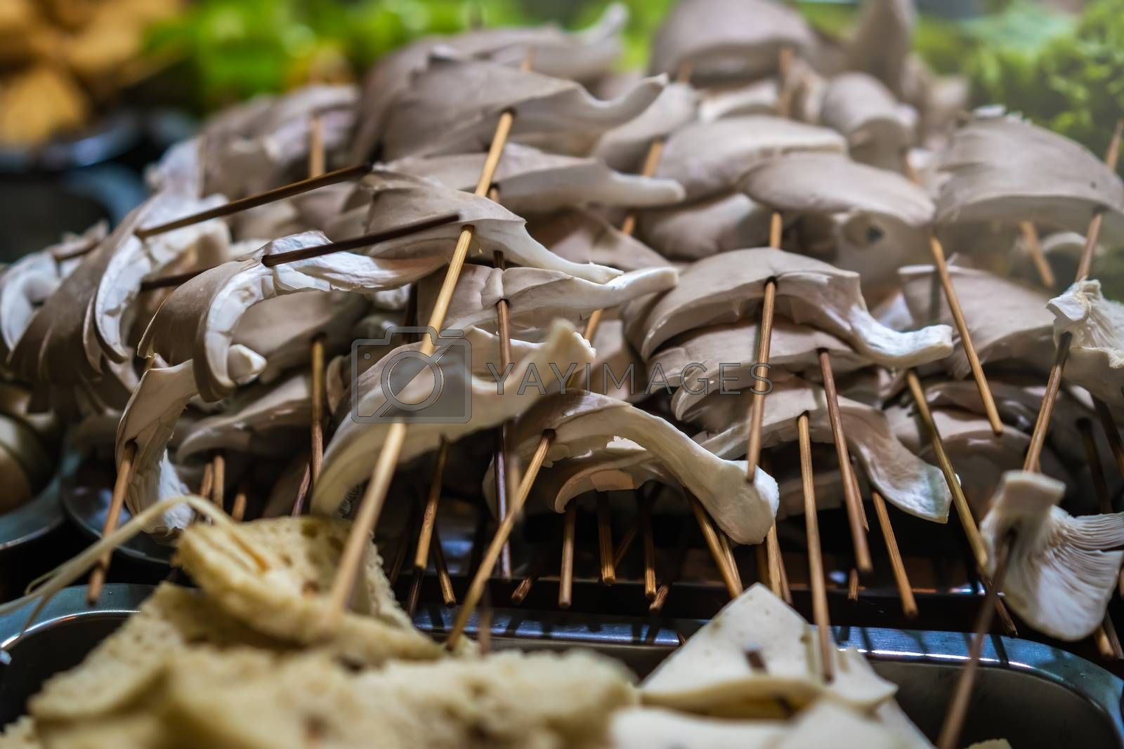 Freshly cut mushrooms on wooden sticks, ready to be grilled on the street in the Muslim Quarter, Xian town, China