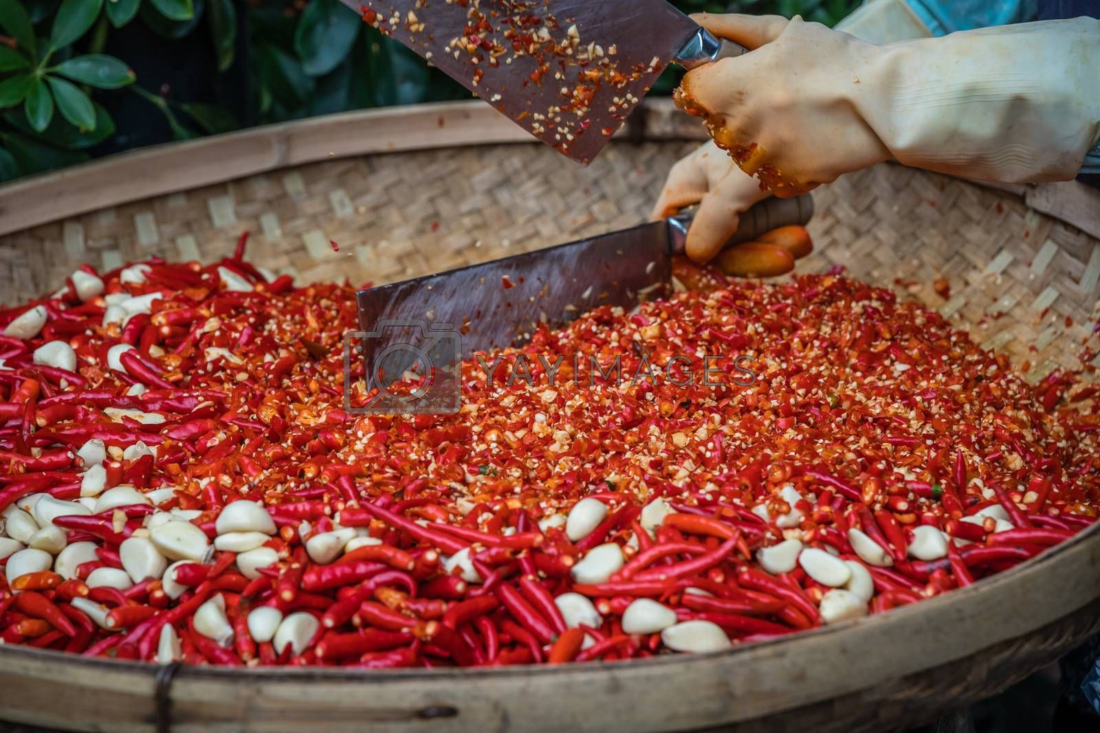 Chillies and garlic being chopped in a wicker bowl by pawopa3336