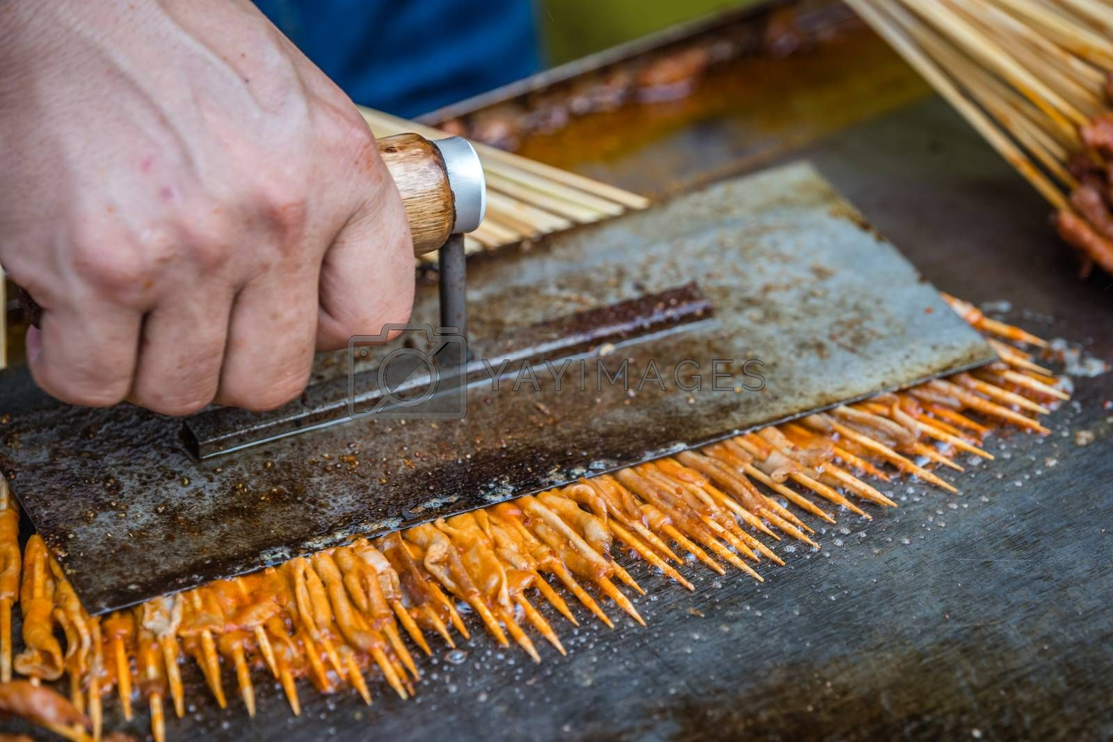 Portions of raw meat, vegetables and seafood on wooden sticks cooked and fried on a hot plate on the street food market in the Muslim Quarter, Xian town, China