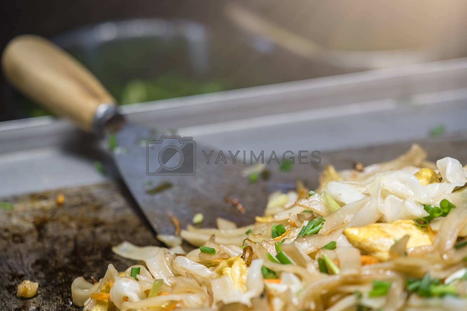 Cut onion and vegetables, egg and noodles cooked and fried on a hot plate on a street food stall in China