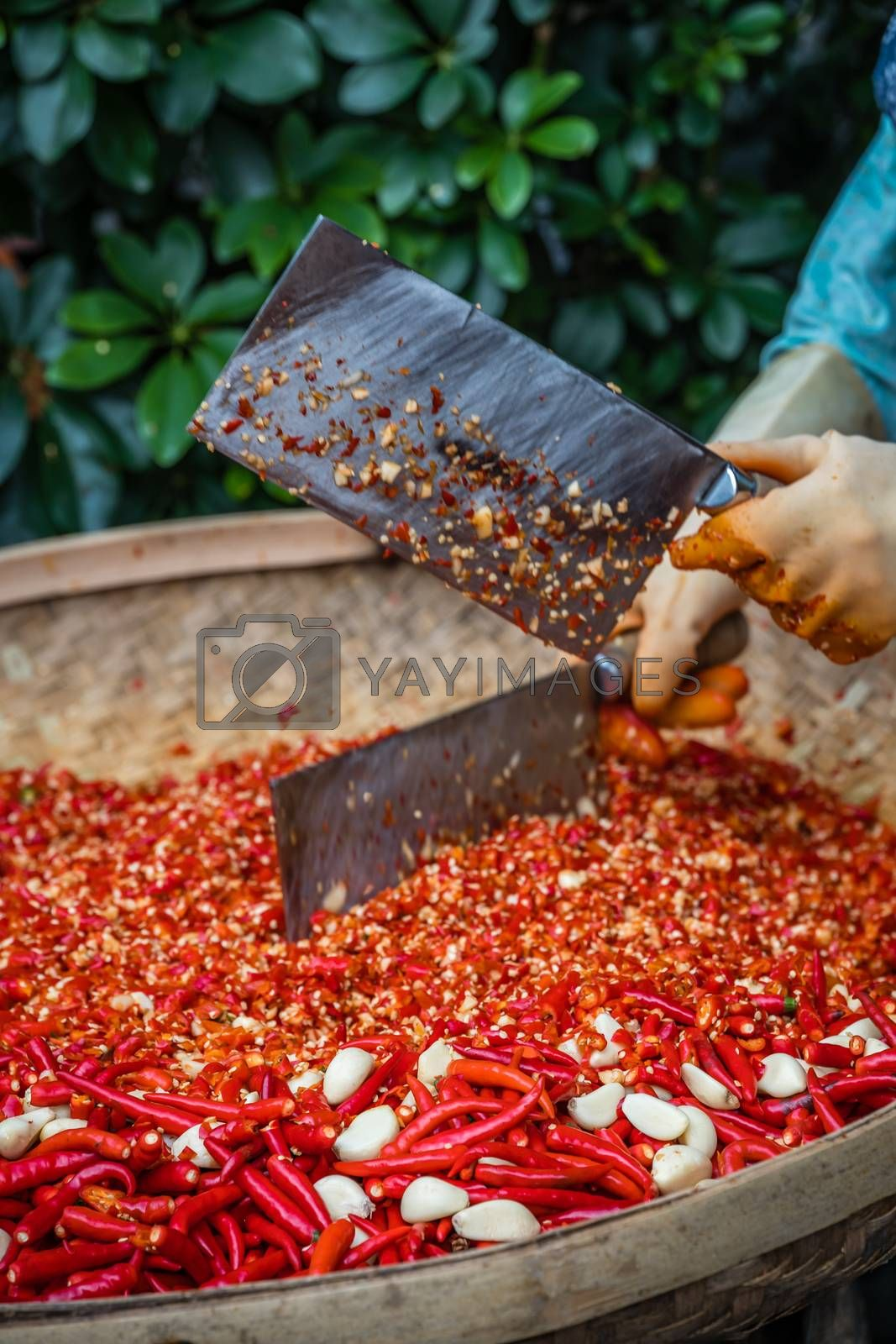 Chillies and garlic being chopped by female worker in a wicker bowl on the street market in Yangshuo town, China