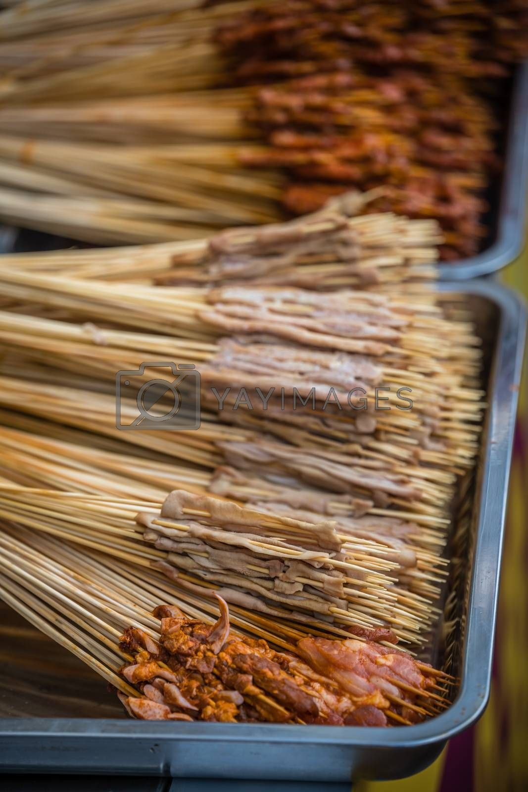 Portions of raw meat, vegetables and seafood on wooden sticks, ready to be grilled on the street in the Muslim Quarter, Xian town, China