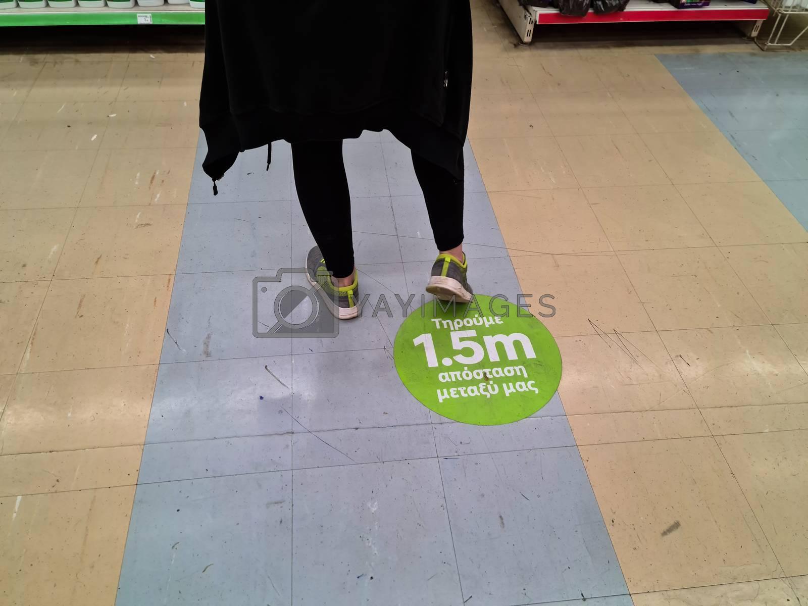Floor sticker suggesting customers keep 1.5 meters away inside store as Coronavirus measures affect business & daily life.