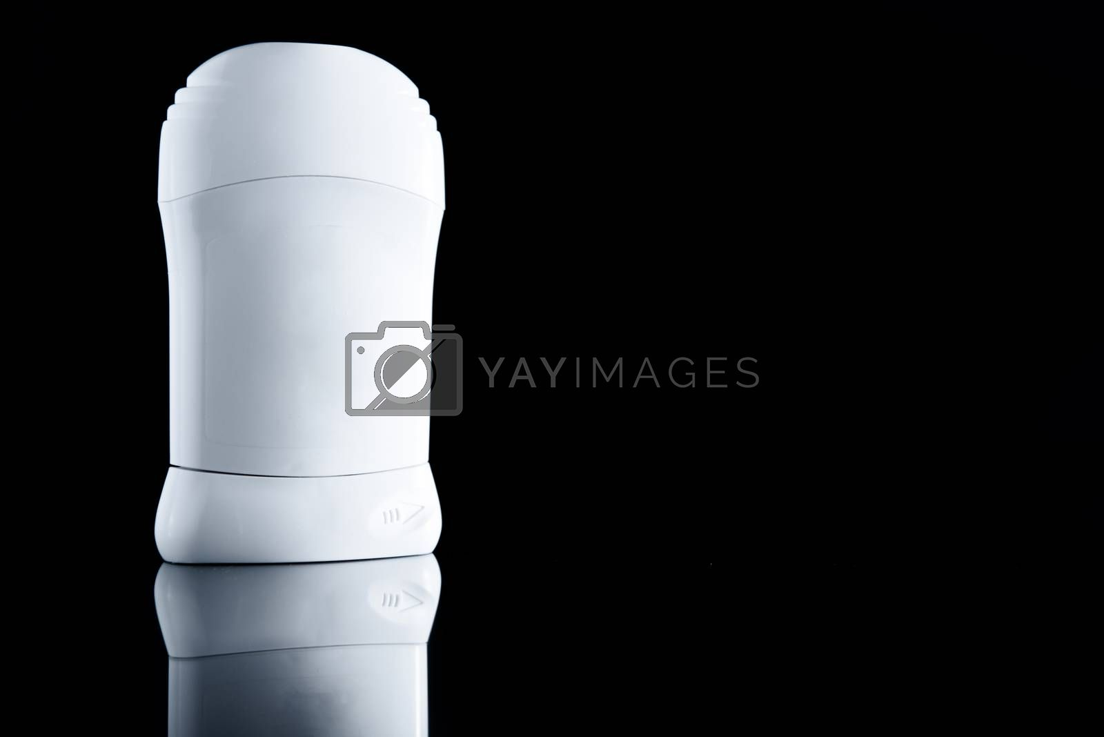 White antiperspirant deodorant standing on black background. Skin care concept with copy space