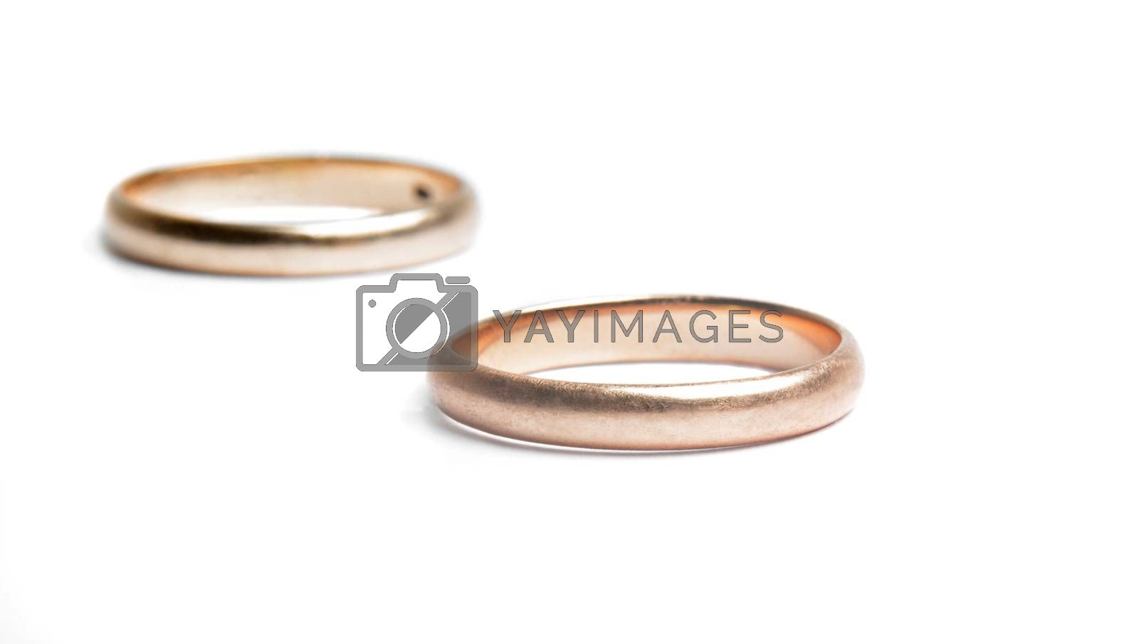two worn golden rings on white