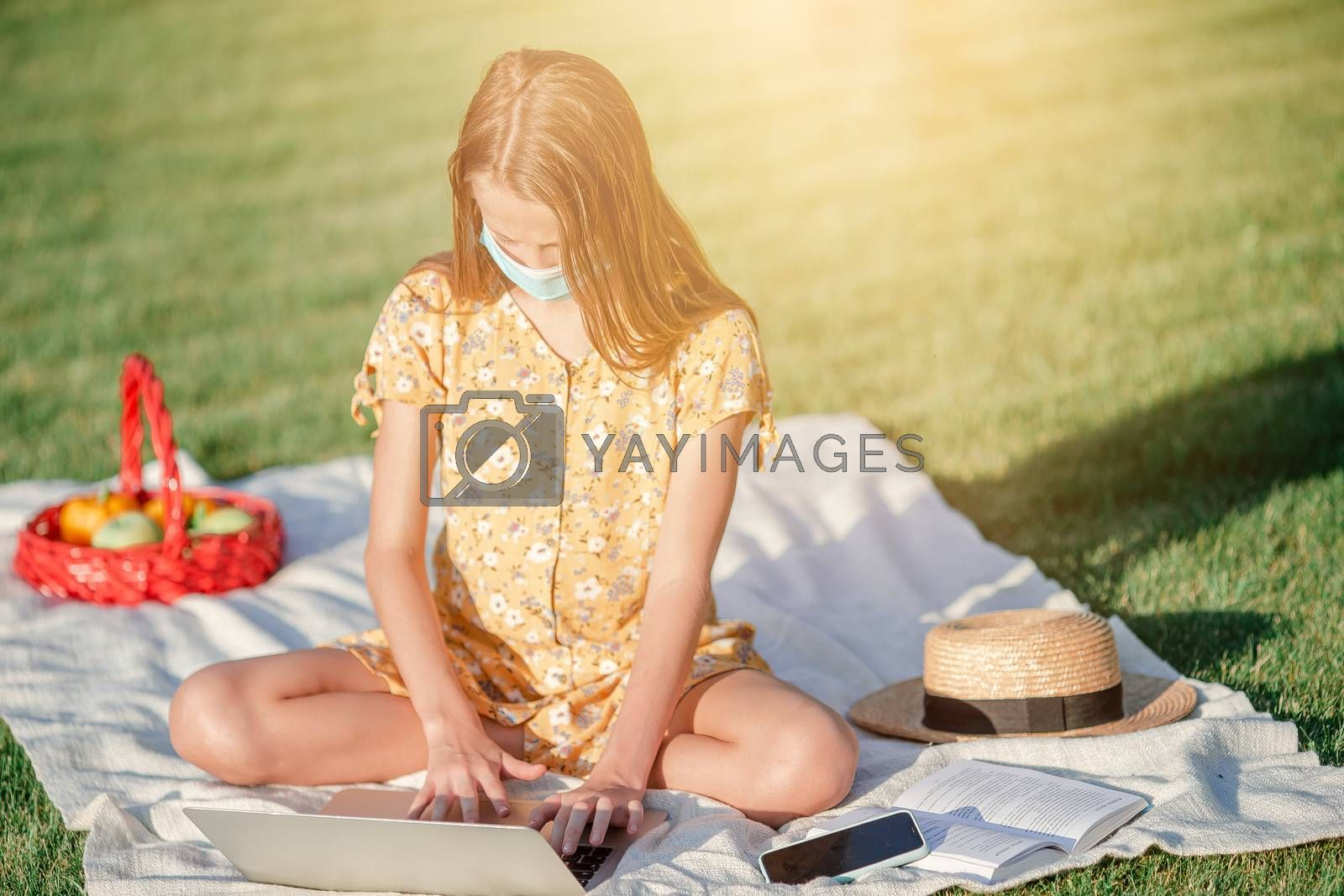 Little girl wearing a protective mask outdoors because of the coronavirus pandemic. Child using laptop to study. Online education and distance learning for kids.
