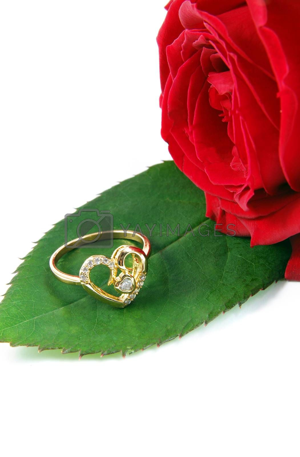 wedding ring with rose over white surface