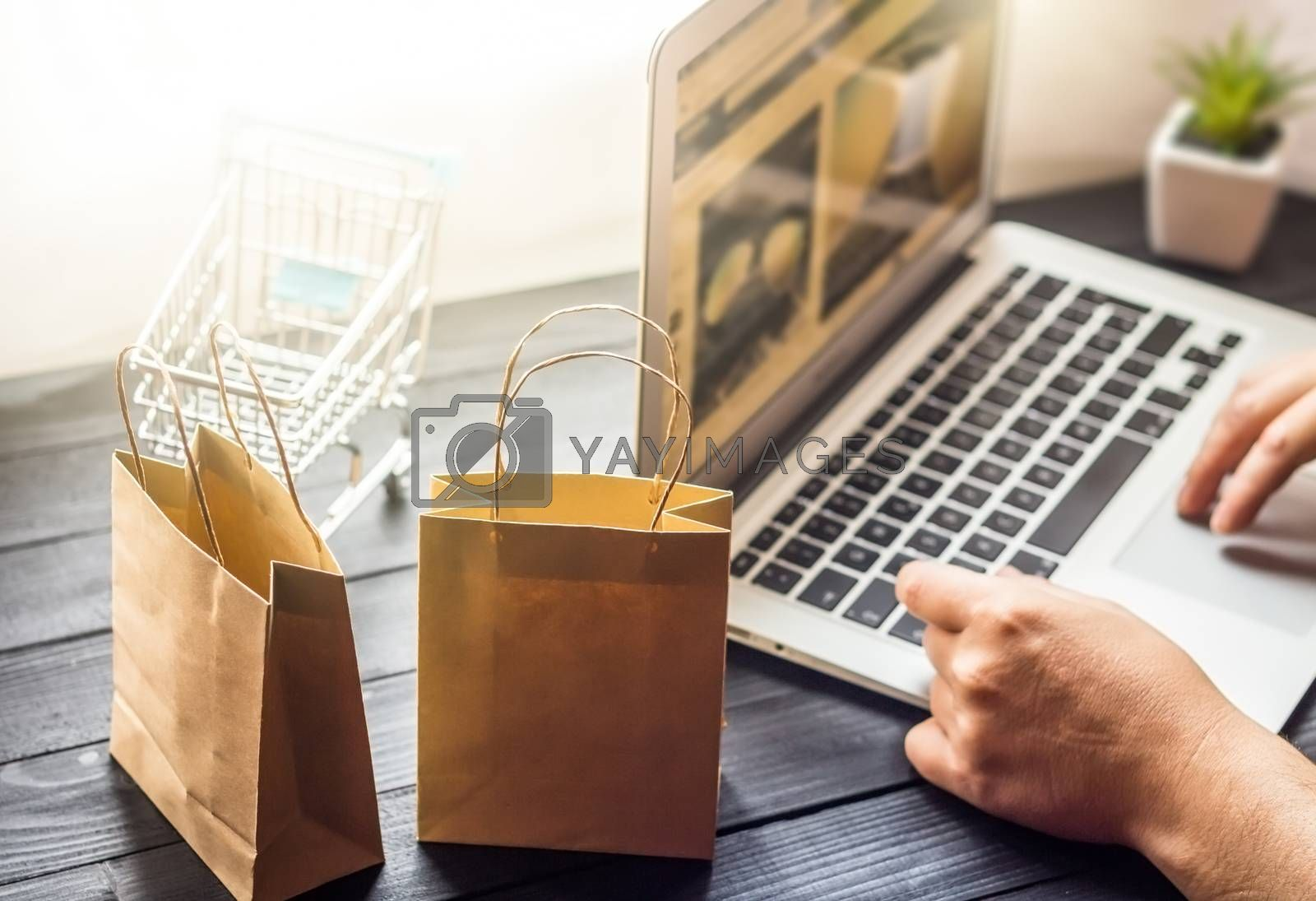 Vienna Austria June.16 2018, Online shopping concept, young men using laptop and holding credit card , selective focus on shopping bags
