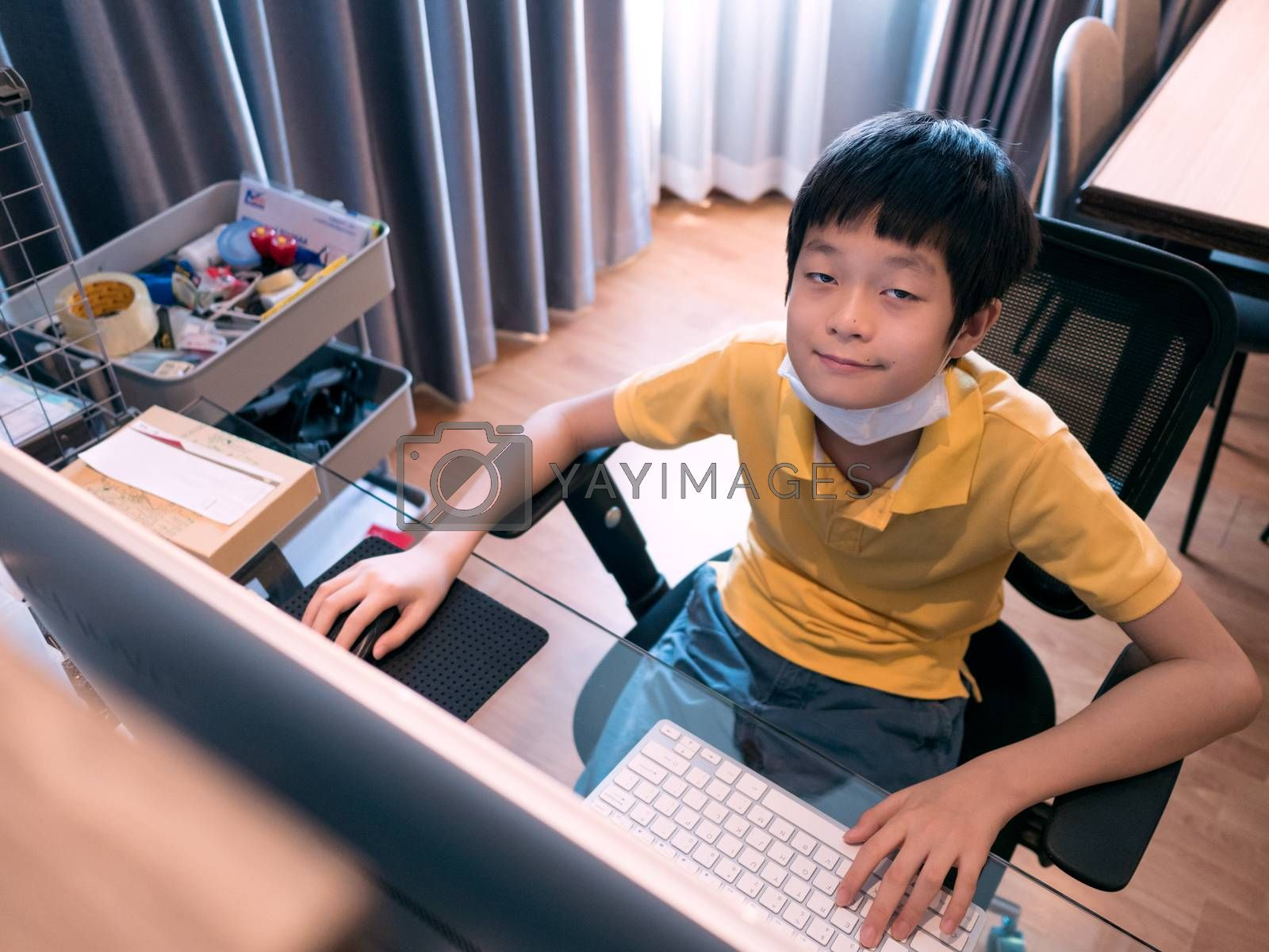 cute asian boy hanging face mask on neck, looking at camera, sitting at desk in living room, using pc for studying online with monitor on blurred foreground, high angle view . Study online, stay home concept.