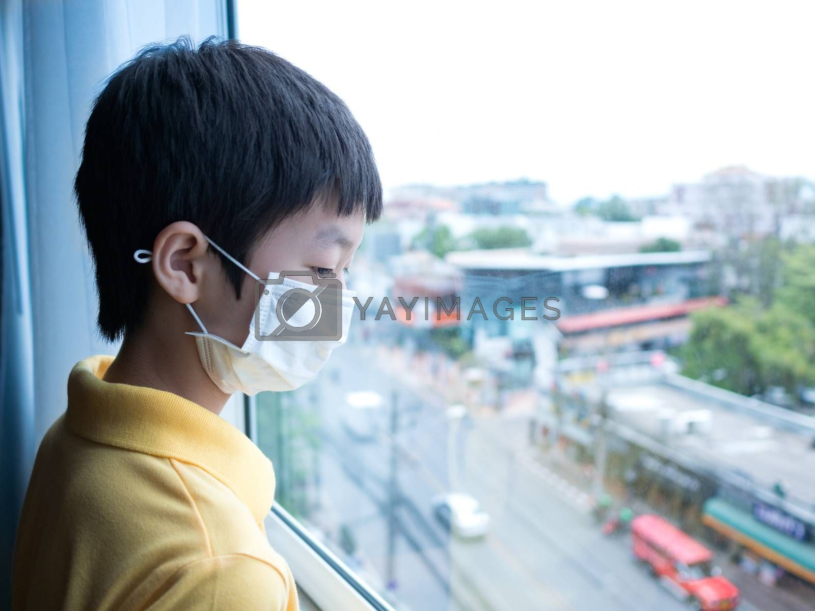 Cute asian young boy with yellow shirt,  wearing medical mask, standing idle in front of close window, looking through window, view from high building. Feel bored , long stay at home concept.