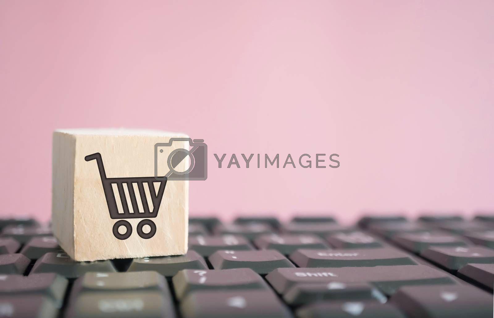 Closed up shopping cart icon on wood cube on computer keyboard. Online shoping business technology. by Suwant