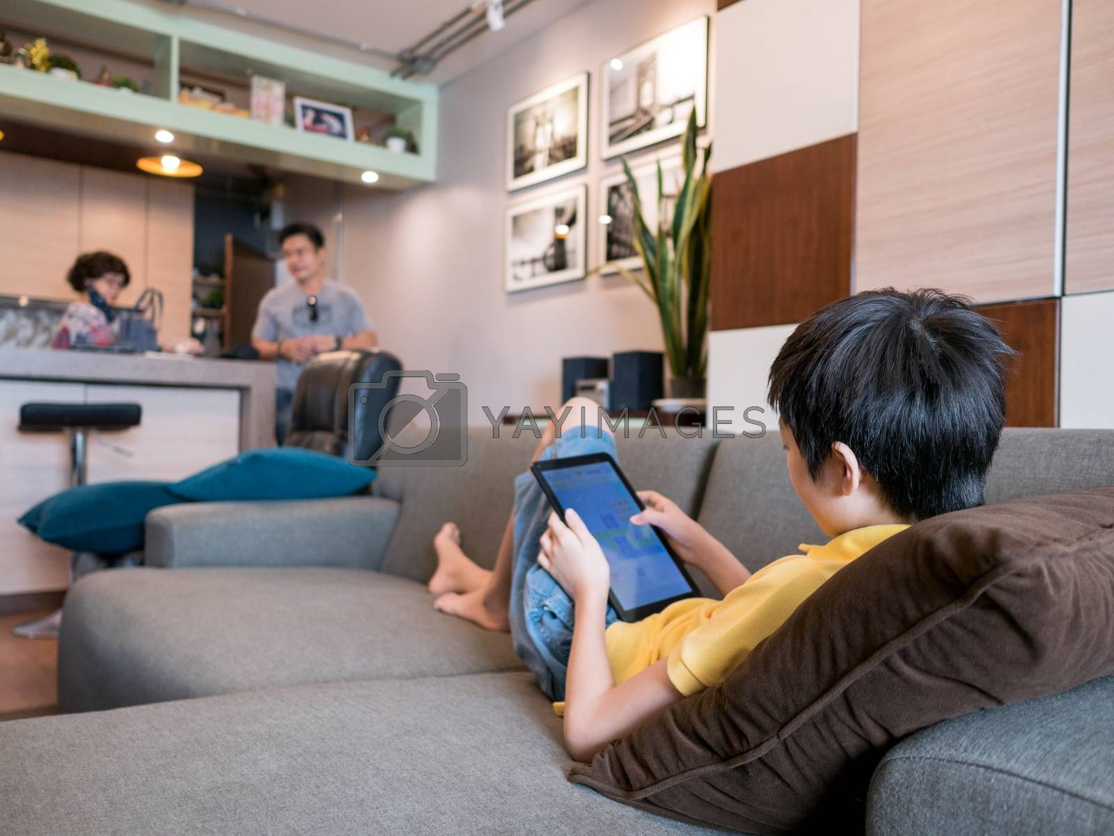 cute asian boy lying on sofa in living room at home, using tablet, parents on blurred background. Study online, stay home concept.