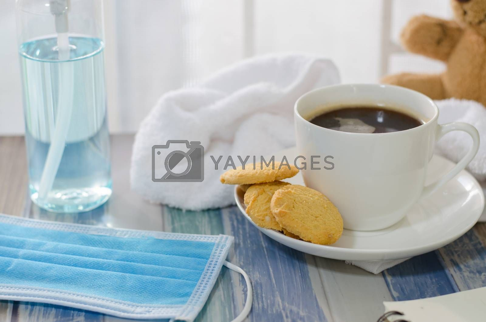 Hot coffee cup with butter cookies and mask alcohol in holiday ideas, wooden holiday house tables to stop the Covid-19 virus.