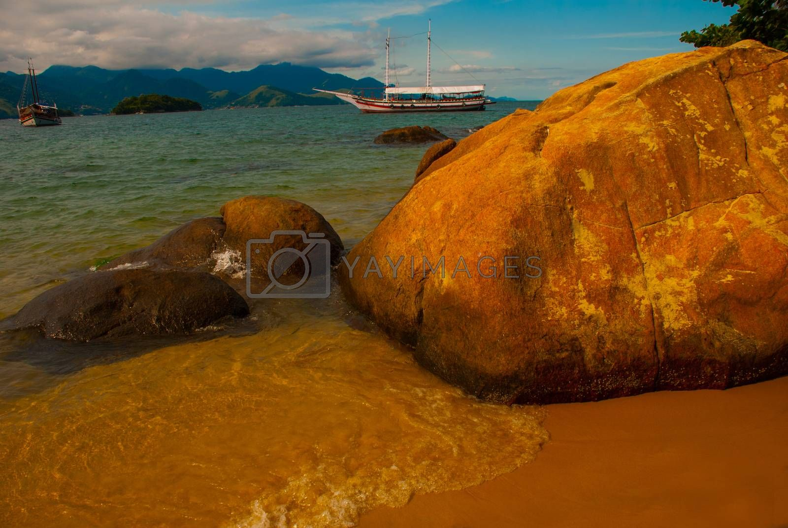 Ilha Grande, Brazil: In the sea stylized ships with tourists. Beautiful tropical beach with rocks on the island, Rio de Janeiro state, Brazil