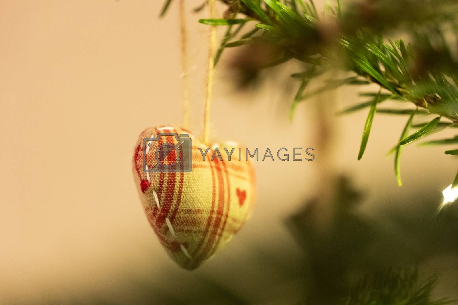 A fabric heart shaped Christmas Tree Decoration hanging from a tree