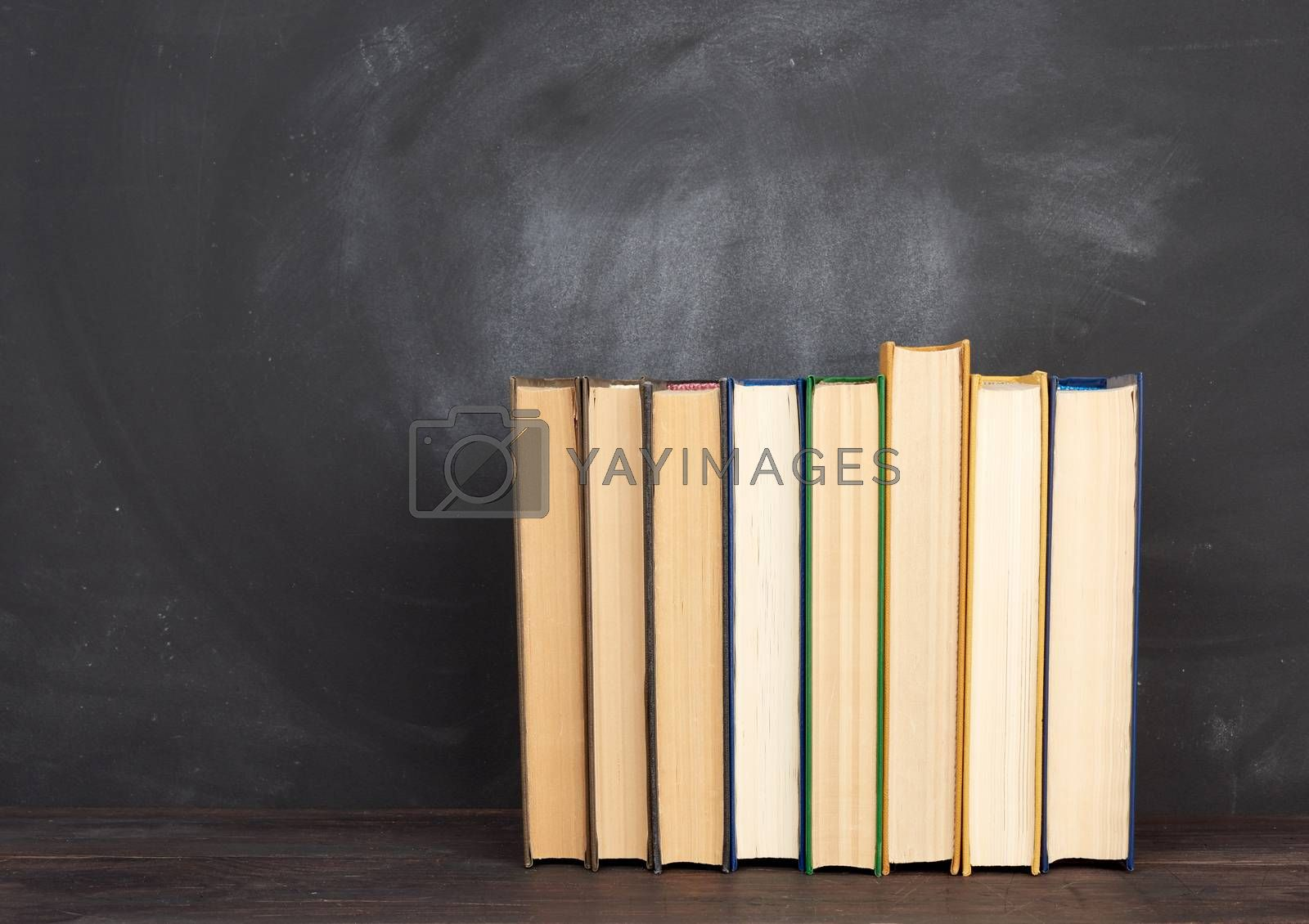 various hardback books on the background of an empty black chalk board, place for text, back to school