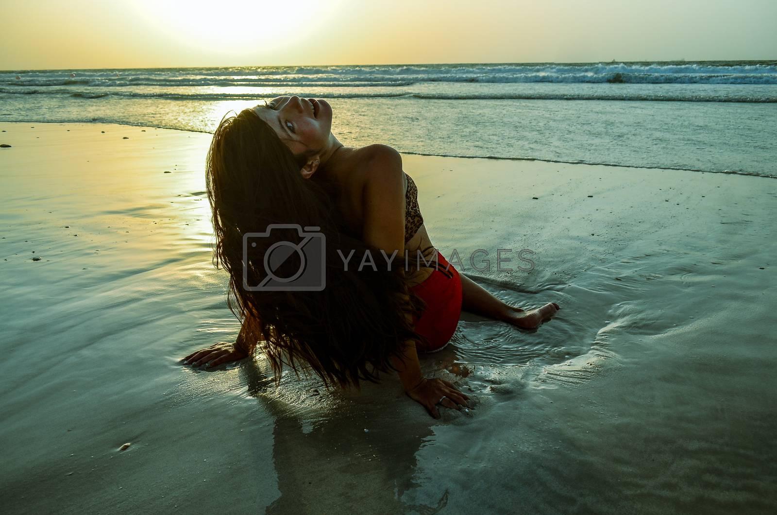 beautiful girl sitting on the beach at sunset