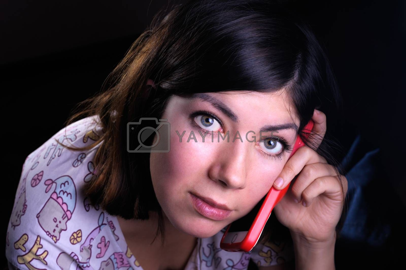 cute young woman with black hair and green eyes talking on a cell phone in a red case