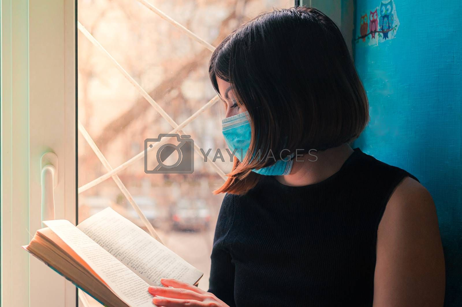 a dark-haired girl in a black dress sits in a surgical mask at the hospital window and reads a book